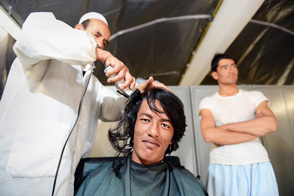 An officer cadet has his hair cut on day one of his training