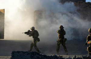 Royal Marines commandos mount an attack on an enemy village using cover from a smoke grenade [Picture: Petty Officer (Photographer) Sean Clee, Crown copyright]
