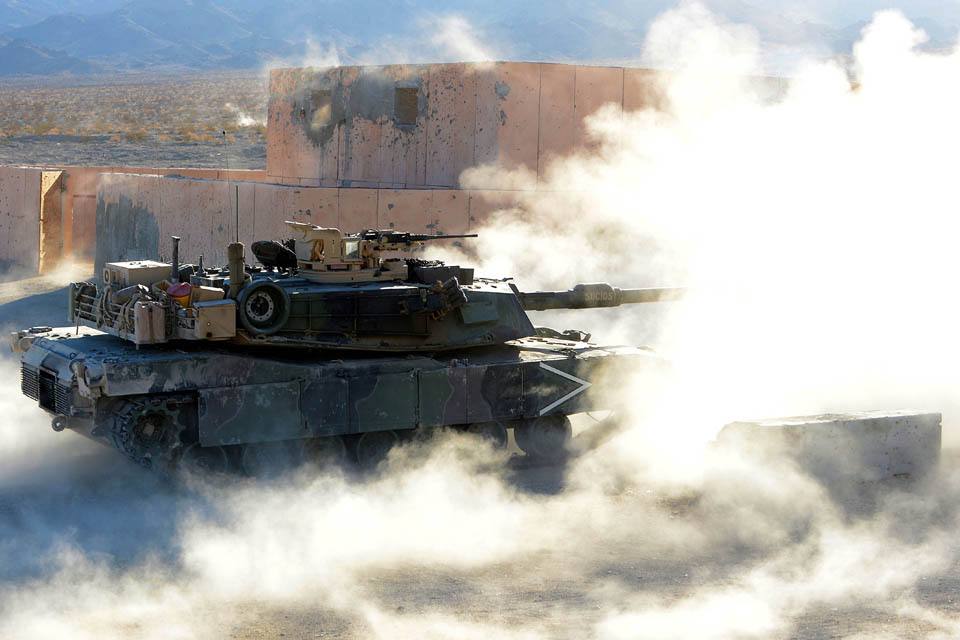 An American M1 Abrams tank fires on an enemy position