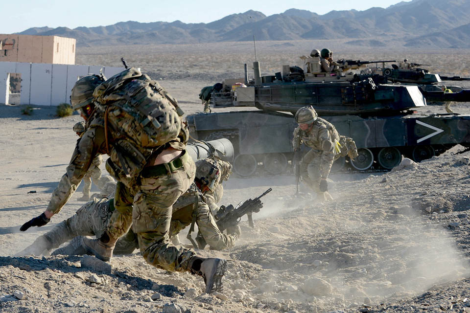 Royal Marines commandos attack enemy positions with support from an American M1 Abrams tank