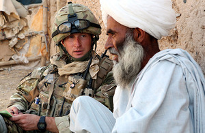 Sergeant Wayne Jackson Royal Marines, a troop sergeant with Mike Company, 42 Commando, talks with a local man during Operation ZAMROD OLAI in northern Nad 'Ali, Helmand province