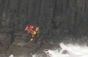 Royal Navy Search and Rescue aircrewman Petty Officer Marcus 'Wiggy' Wigfull retrieves stranded sightseers from a cliff face in the Inner Hebrides