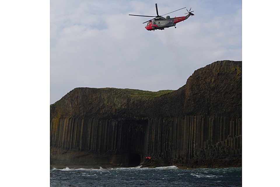 Rescued sightseers are winched aboard HMS Gannet's Sea King helicopter from the rocks below