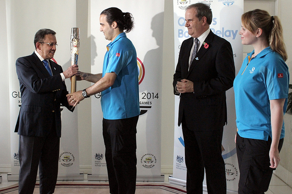 Louis Rosa from the Queen's Baton Relay Team hands over the Baton to His Royal Highness Prince Sufri
