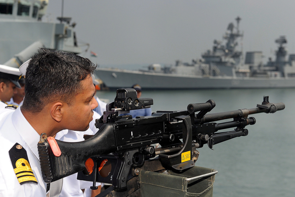 An Indian naval officer examines a British general purpose machine gun