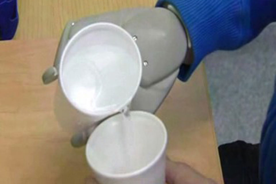 Corporal Garthwaite demonstrates his delicate control of the bionic arm by pouring water from one polystyrene cup into another