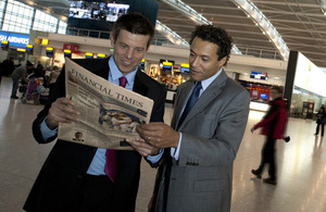 Two businessmen read the FT at Heathrow Airport