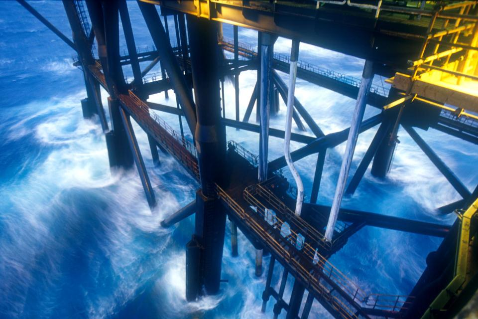 The sea crashing against the legs of an offshore oil platform