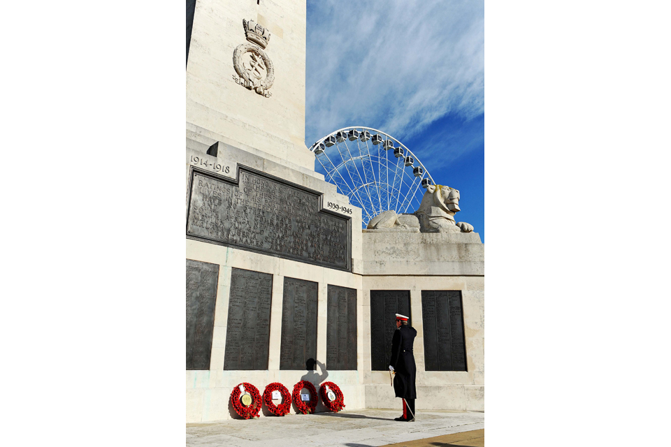 A serviceman pays his respects at the Plymouth War Memorial