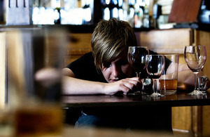 A drunken white female slumped over a pub table.