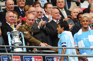 Corporal Mark Ward shakes hands with Carlos Tevez, the captain of Manchester City, prior to presenting the trophy to the 2011 FA Cup winners