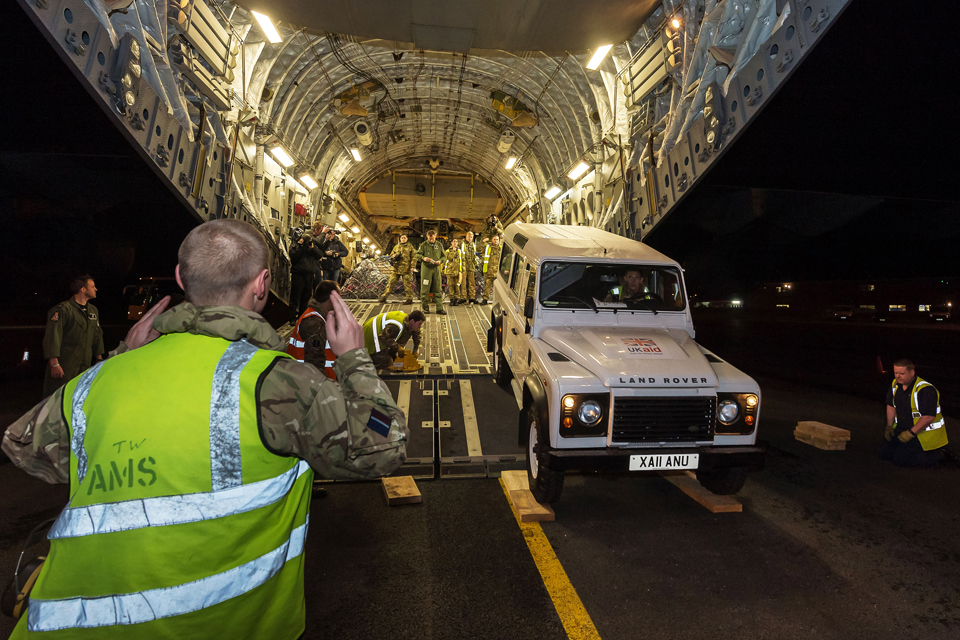 A Land Rover is loaded into the hold of the C-17