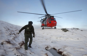 A serviceman approaches HMS Gannet's Search and Rescue helicopter