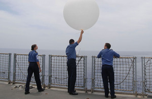 Able Seaman Kerry Woollard, Lieutenant Lee Newman and Leading Seaman Chris Edmonds release a weather balloon on board HMS Albion