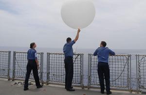 Able Seaman Kerry Woollard, Lieutenant Lee Newman and Leading Seaman Chris Edmonds release a weather balloon on board HMS Albion