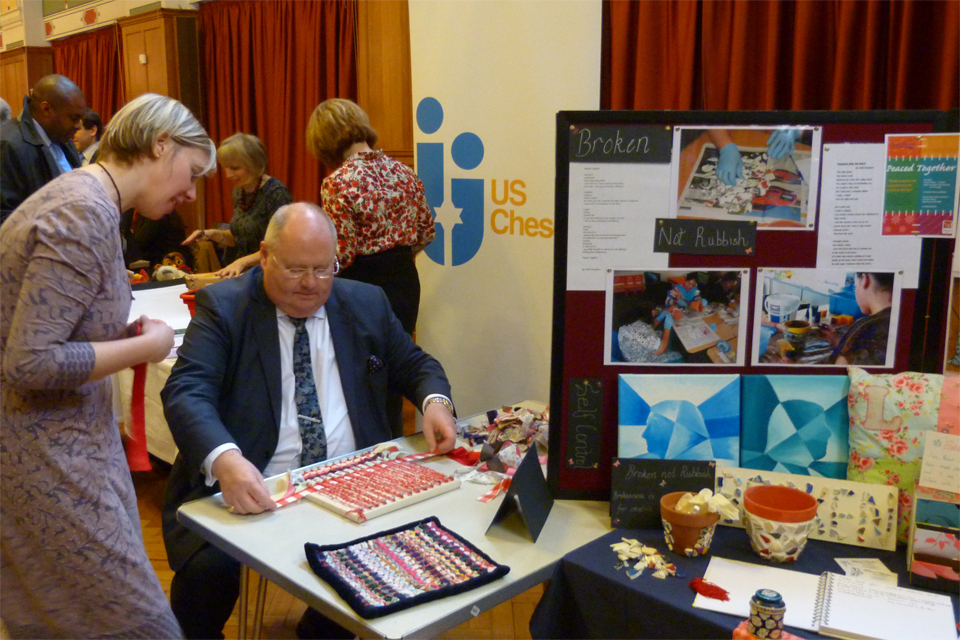 Eric Pickles interacting with the Peaced Together stall, which looks at the process of restoration and hope.