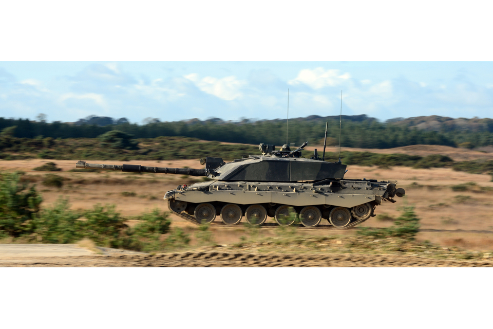 A Challenger 2 main battle tank races across the Five Tips Range