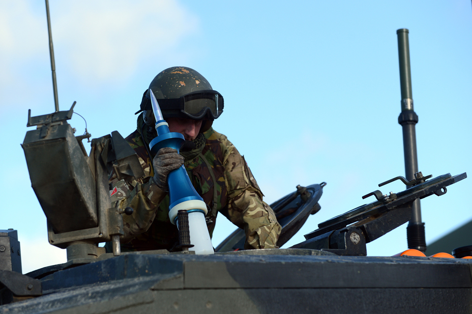A reservist passes an armour-piercing round through the hatch of a Challenger 2