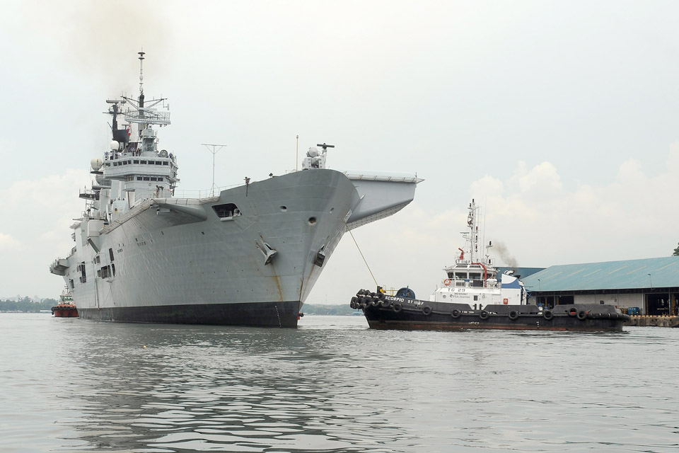 Tug boats escort HMS Illustrious safely from her berth