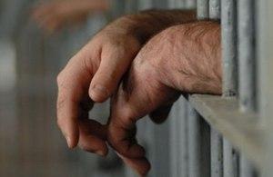 Image of prisoner behind bars