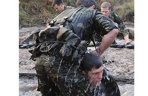 One of the Royal Marines Physical Training Instructors is helped out of a submerged water pipe during the Tarzan assault course phase of the four commando tests