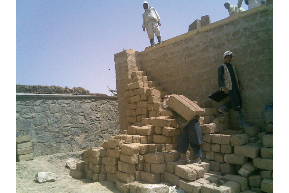 Afghan workers using traditional construction techniques
