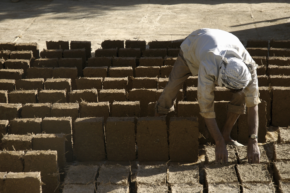 An Afghan worker uses traditional adobe blocks