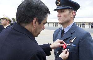 Royal Air Force Flight Lieutenant Ian Abson receives the Croix de la Valeur Militaire with bronze star from the Prime Minister of France, François Fillon