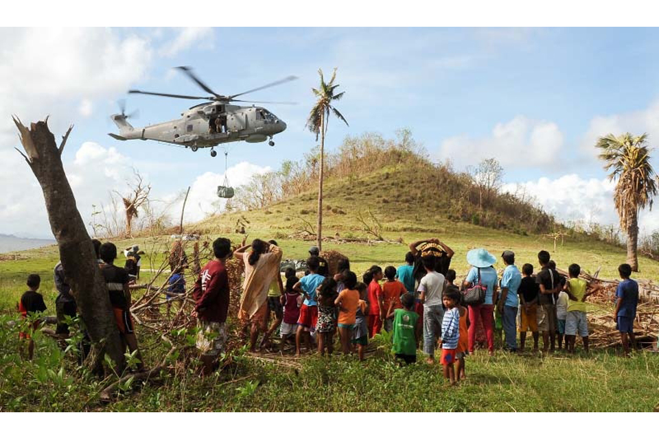 A Merlin helicopter delivers aid to communities on Sicogon Island