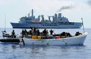 Royal Marines search a pirate skiff packed with fuel drums with RFA Fort Victoria in the background