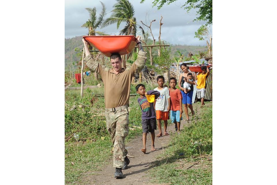 A Royal Marine carrying part of a wheelbarrow