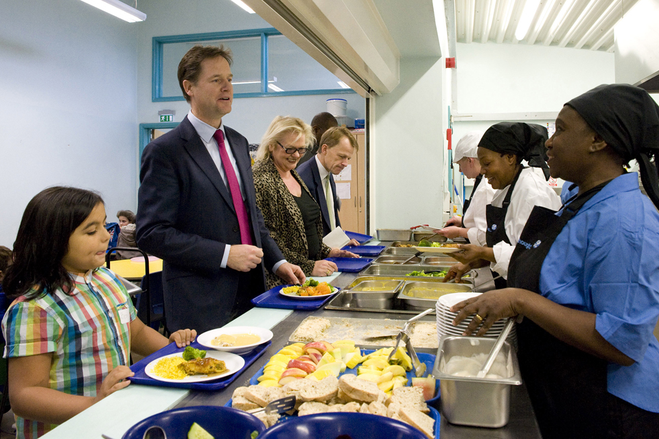 Deputy Prime Minister Nick Clegg eating lunch with students from Walnut Tree Walk Primary School.