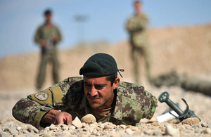 British Army explosive ordnance disposal trainers watch an Afghan soldier conducting search drills
