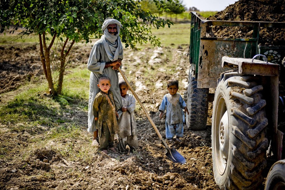 A farmer and his family by a tractor.