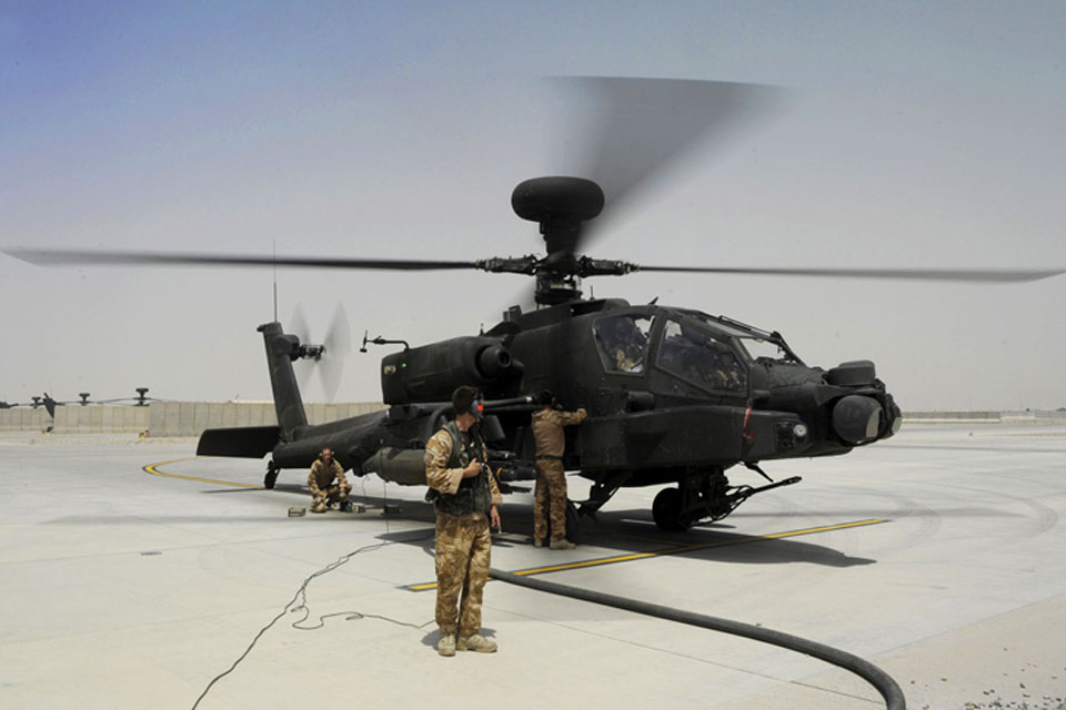 Ground crew check over a British Army Apache attack helicopter