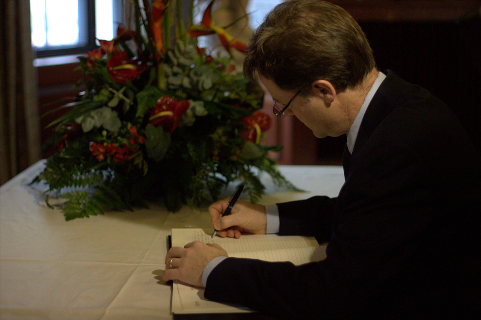 Nick Clegg signing a book of condolence for Nelson Mandela at South Africa House.