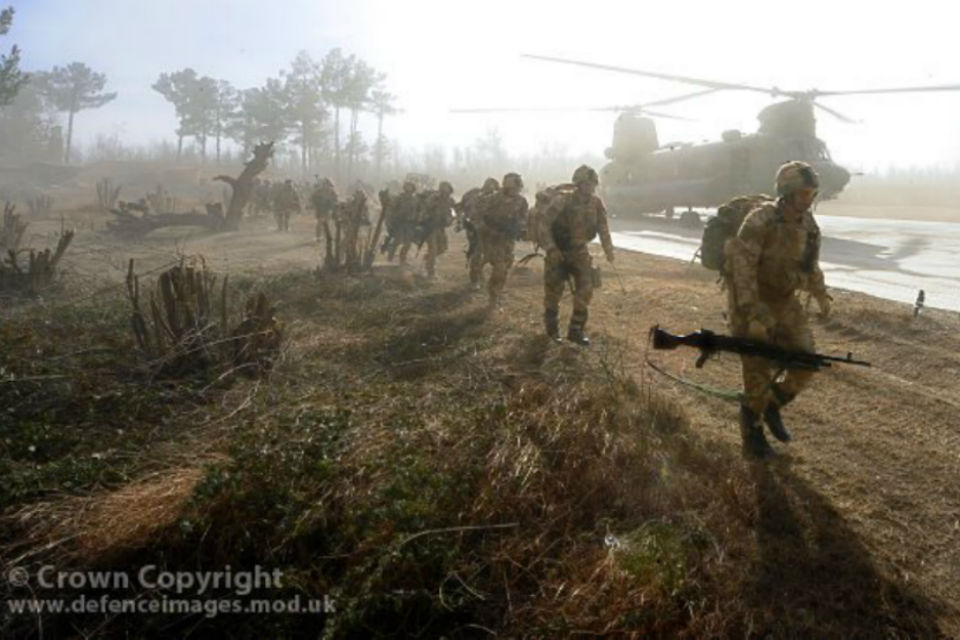 Soldiers in running past a military helicopter.