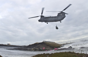 An 18 Squadron RAF Chinook moving bags of aggregate into breached sea defences [Picture: Corporal Jimmy Wise RAF, Crown copyright]