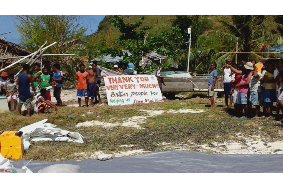 Philippine islanders hold up a sign of thanks
