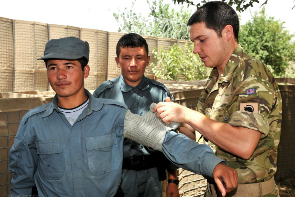 UK soldier showing ANSF soldiers how to bandage an arm.