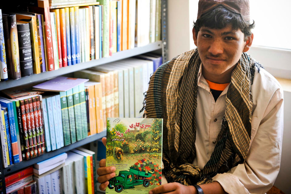 Afghan farmer in an agricultural college holding a book.
