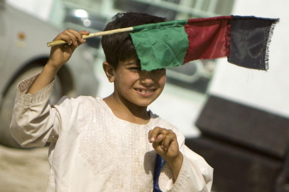 Afghan boy holding a flag.