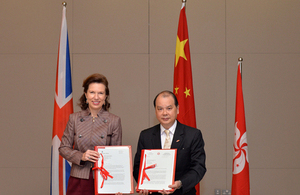 Ms Wilson (left) and Mr Cheung (right) exchange the official letters on the agreement to establish the working holiday scheme.