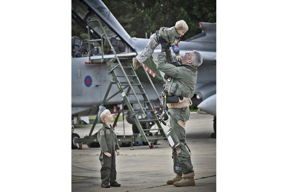 An airman lifts a child