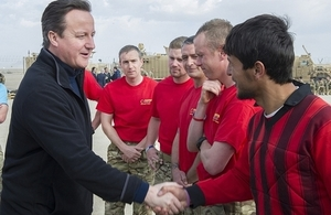 David Cameron shakes hands with British army personnel and a member of an Afghan football team.