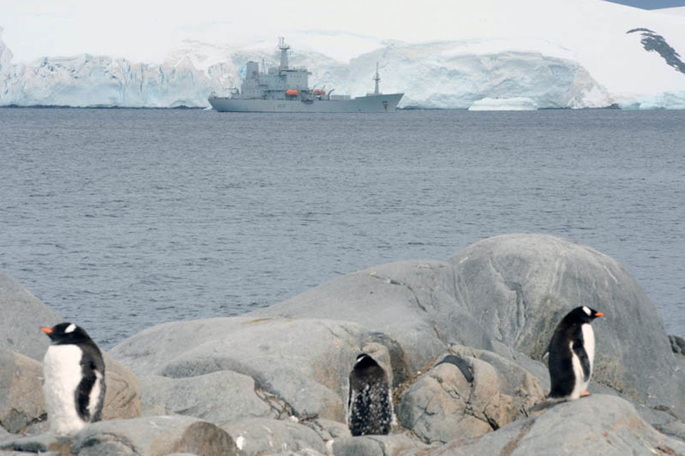 Penguins stand sentry as HMS Scott visits Port Lockroy during her last Antarctic deployment