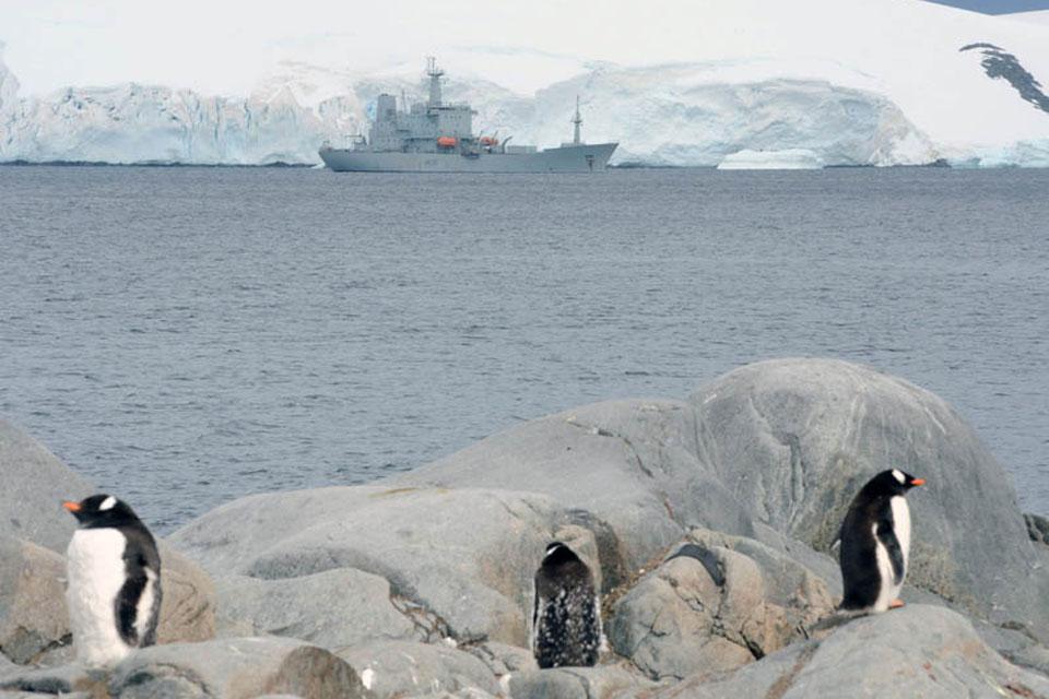 Penguins stand sentry as HMS Scott visits Port Lockroy during her last Antarctic deployment