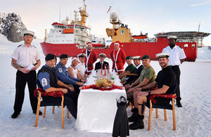 Crew members of HMS Protector sit down to their Christmas dinner on the ice [Picture: Leading Airman (Photographer) Vicki Benwell, Crown copyright]