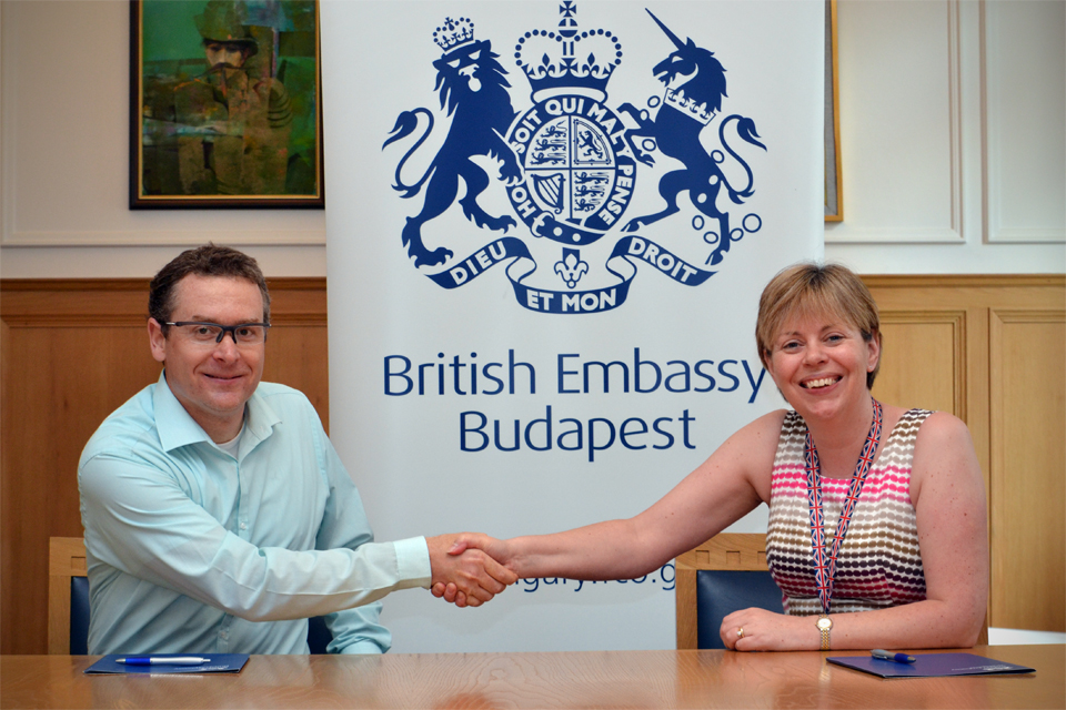 Deputy Head of Mission Theresa Bubbear signing a support contract with Ervin Bonecz, managing director of 90 decibel Project