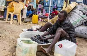 A teenager displaced by violence washes clothes in a basin in South Sudan, January 2014. Picture: K McKinsey/UNCHR